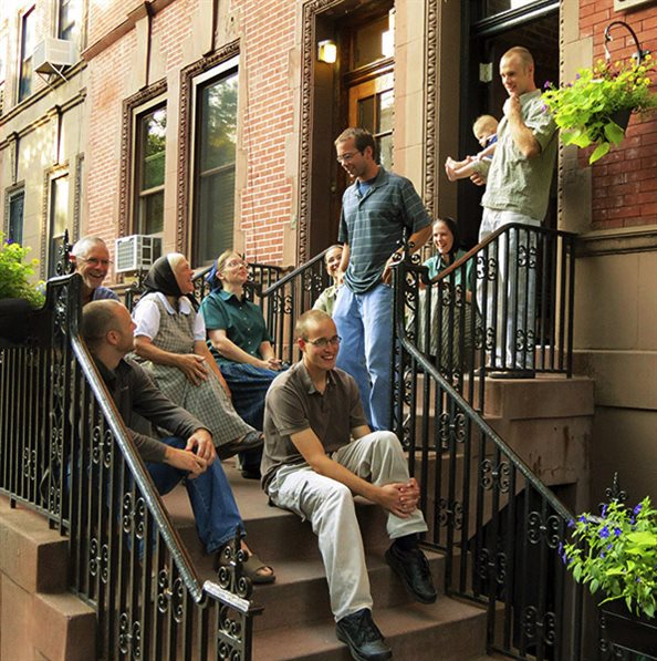 members of an urban community house sitting on their front stairs