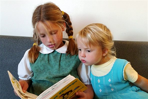 two children looking at a book