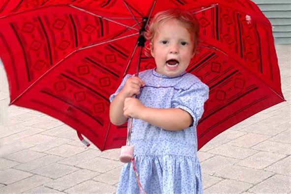 a little girl holding a big red umbrella