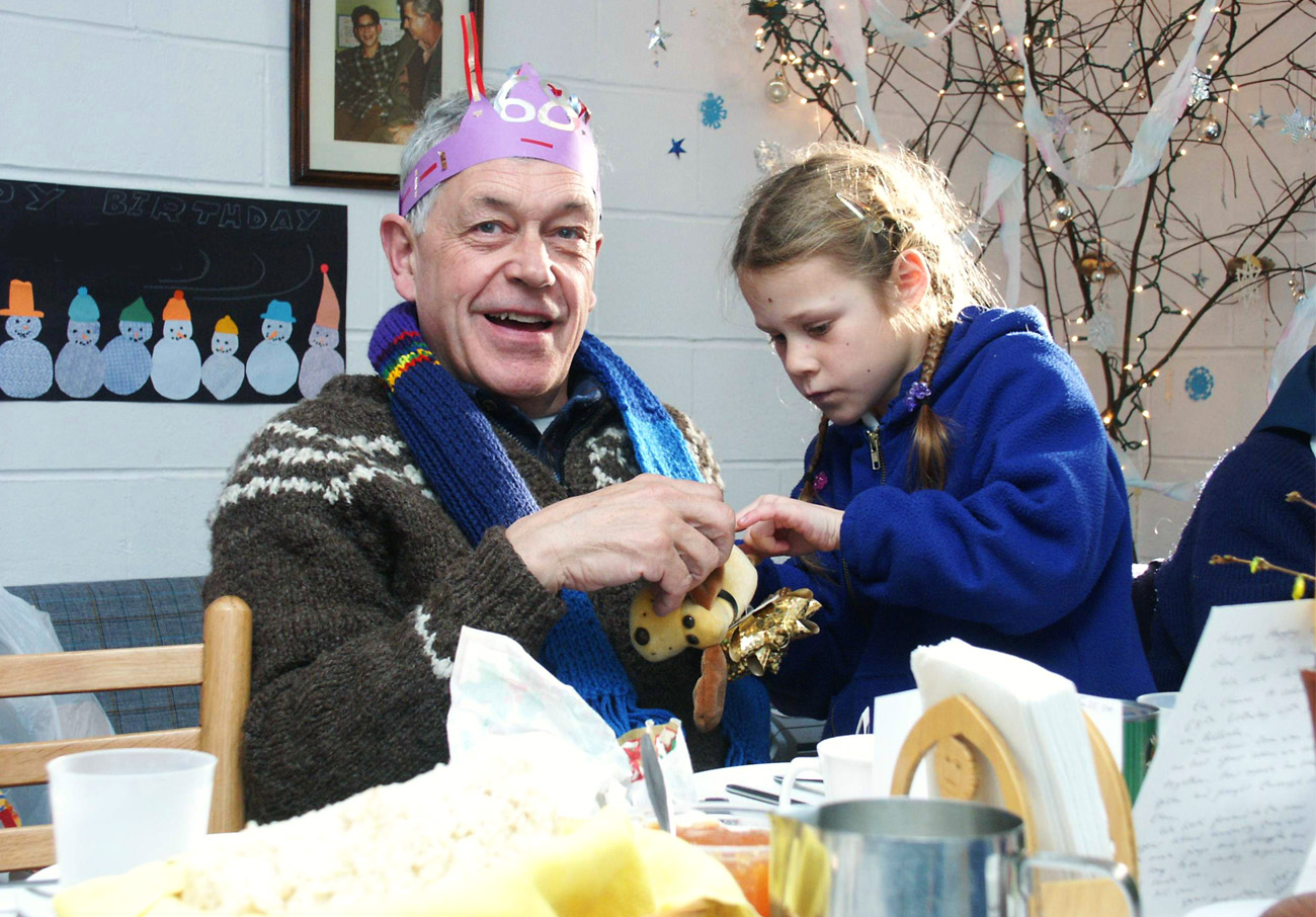 An elderly man celebrating his birthday and a child offering him a package
