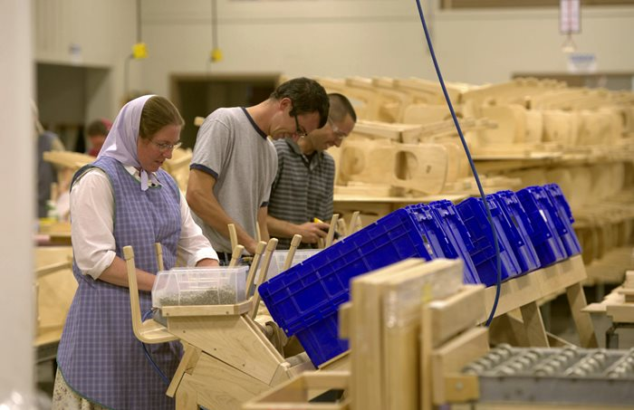 Three adults preparing Community Playthings chairs for shipment in a Bruderhof work shop