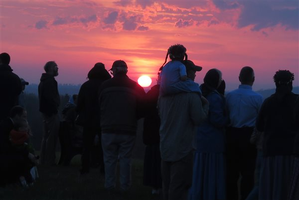 A group of community members gathered on a hilltop to watch the sun set