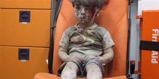 Photograph of a young boy sitting in an ambulance in Aleppo. He is covered in dust and blood.