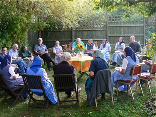 an outdoor gathering of some adult members of an intentional Christian community