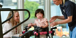 two women helping a young girl with disabilities in a specialized stander