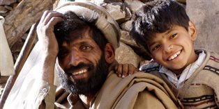 a man and young boy outside the earthquake induced rubble of their home in Pakistan