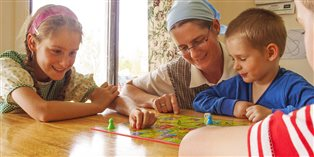 Dori and her children playing snakes and ladders around the living room table