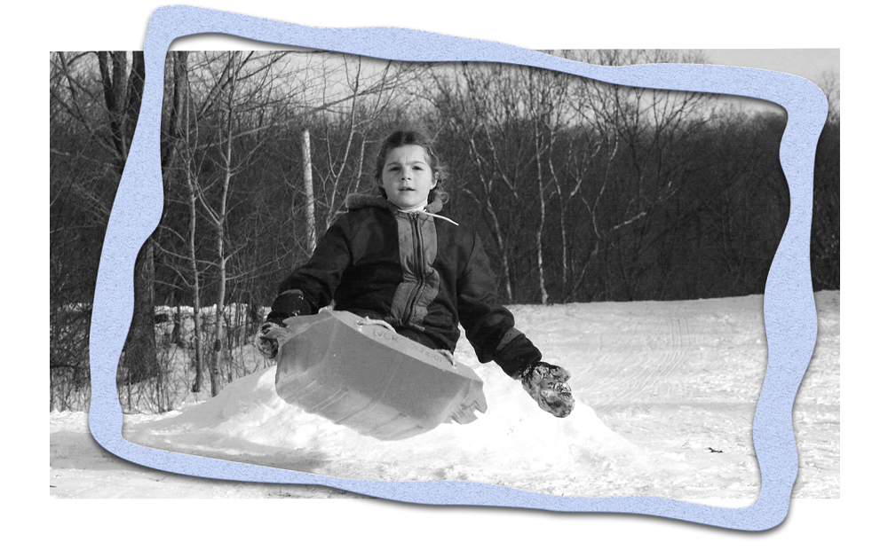 Shana going over a jump while sledding as a child