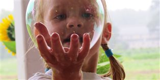 child looking through a soap bubble