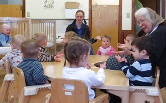 Oma Lydia teaching finger games to a group of one-year-olds