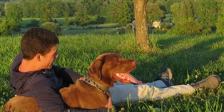 a boy and his dog sitting on a hilltop
