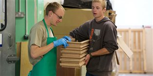 Image of two young men working in a wood shop