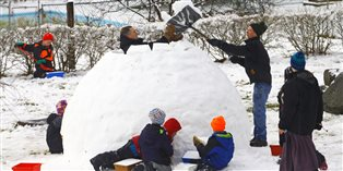kids and adults from an intentional Christian community building an igloo
