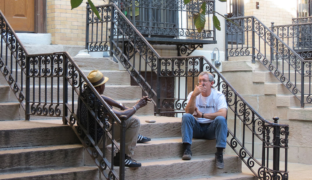 Tim and a friend hang out on the front steps of Harlem House.