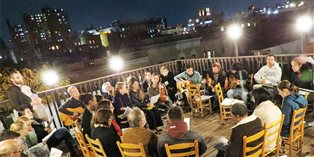 An evening rooftop gathering at Harlem Bruderhof House.